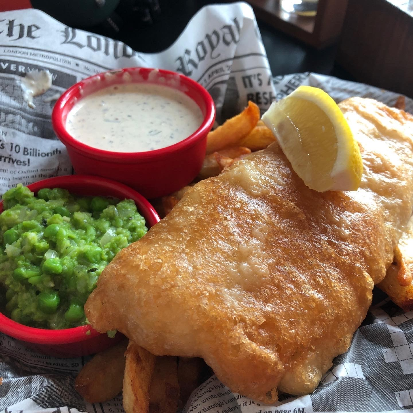Image shows fried fish with chips and green mushy peas
