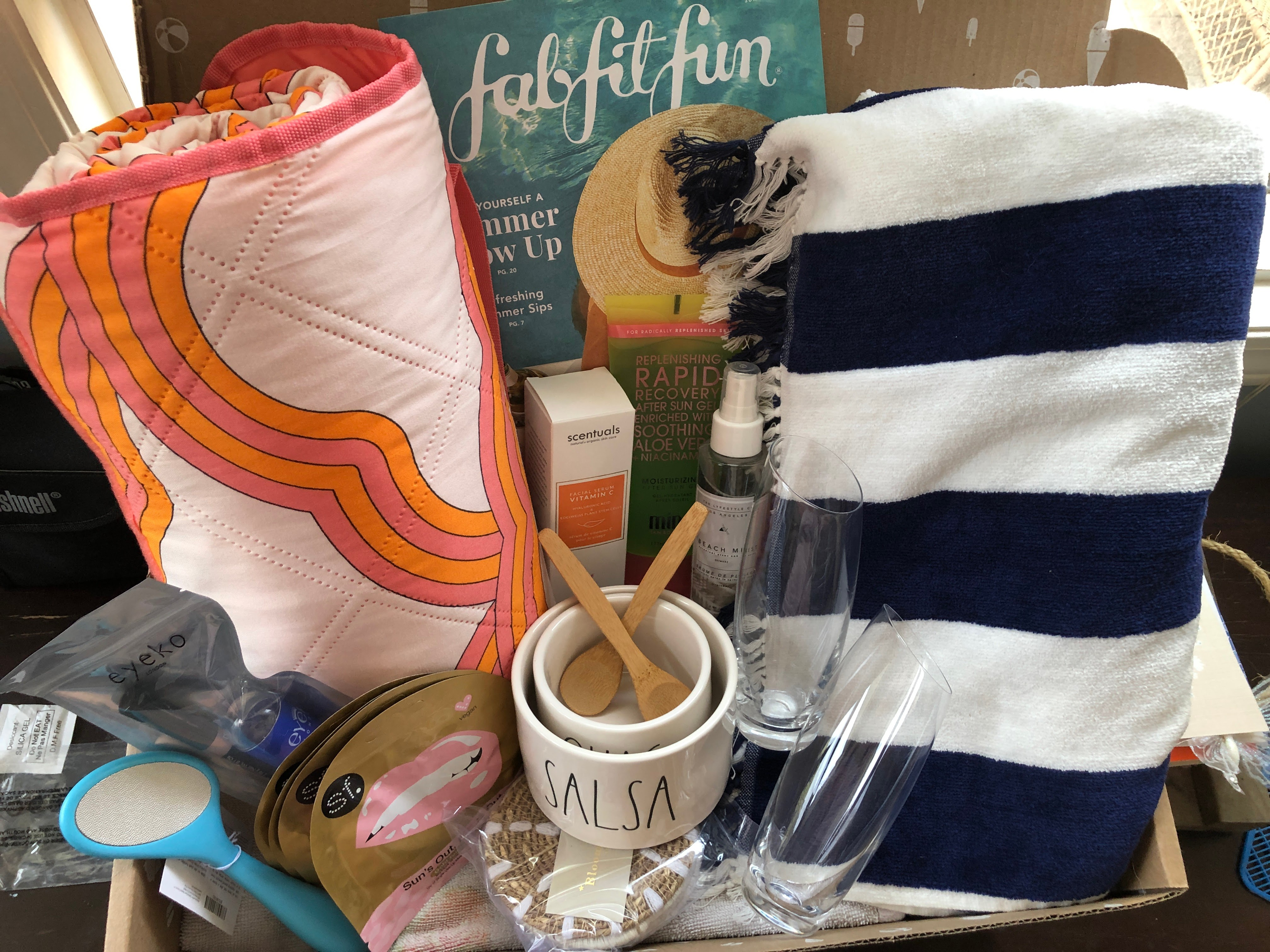 This image shows all the contents of the fitfabfun box.  Most visible are a bright Orange and pink rolled up blanket and a blue and white striped towel.